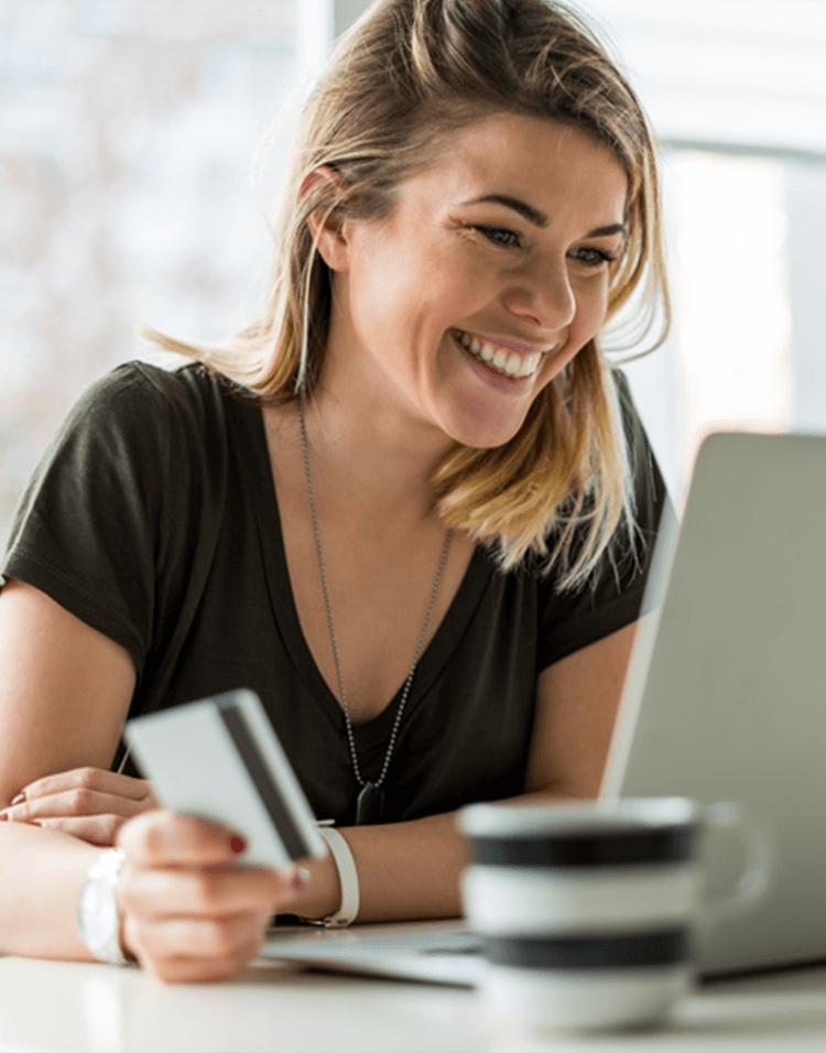 Frau sitzt lächelnd mit Kredtikarte in der Hand vor einem Laptop