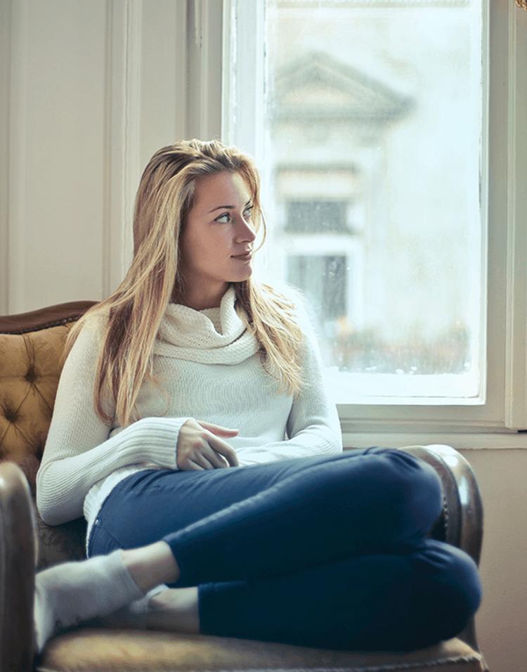 Frau sitzt auf einem Sessel vor dem Fenster