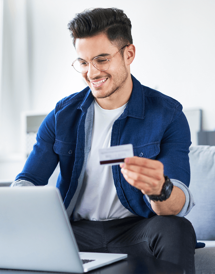 Mann sitzt mit Kreditkarte in der Hand vor dem Laptop