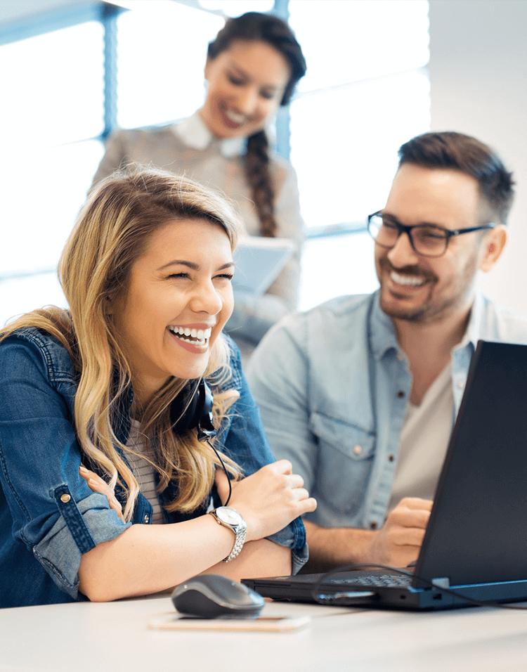 Mitarbeiter lächeln und sitzen vor einem Laptop